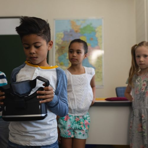 Front view of schoolboy holding and looking at virtual reality headset with his classmates who look him behind  in classroom of elementary school