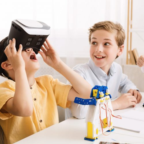 Schoolboy playing with vr glasses in classroom, having break at school