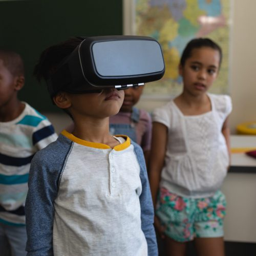 Front view of schoolboy using virtual reality headset whit his classmates behind him in classroom of elementary school