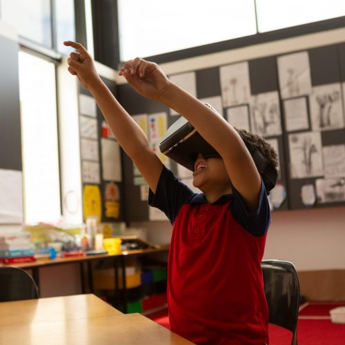 Side view of cute mixed-race schoolboy using virtual reality headset with hands in the air at desk in a classroom at elementary school